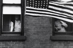 Photograph of people looking out of a building with a large American flag